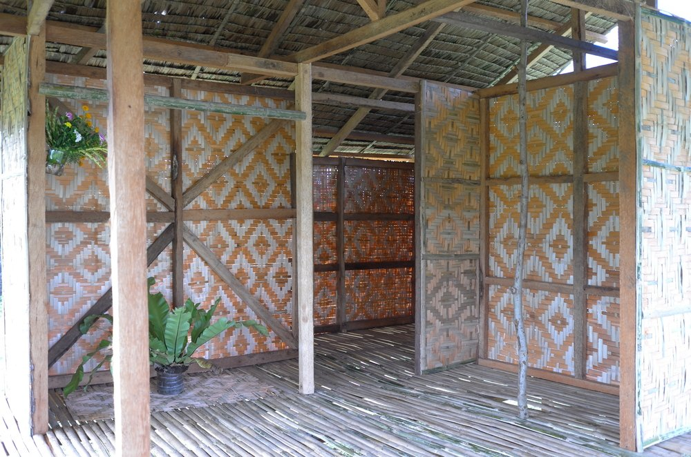 The interior of the hut has wooden pillars and walls made of woven wicker panels.