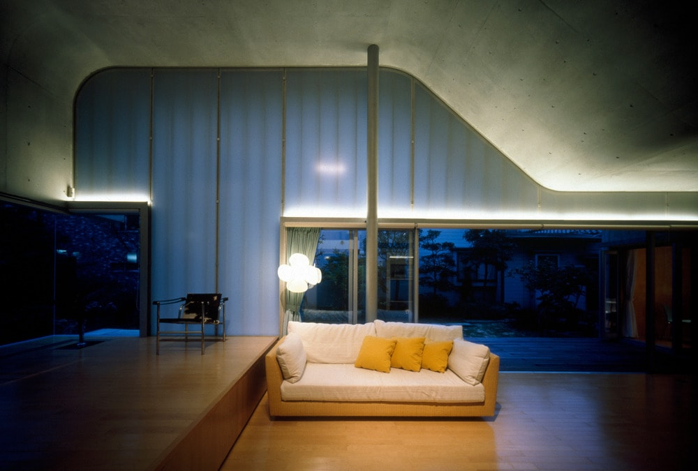 This is a spacious minimalist living room with a simple sofa complemented by the large hardwood flooring and topped with a tall arched concrete ceiling.