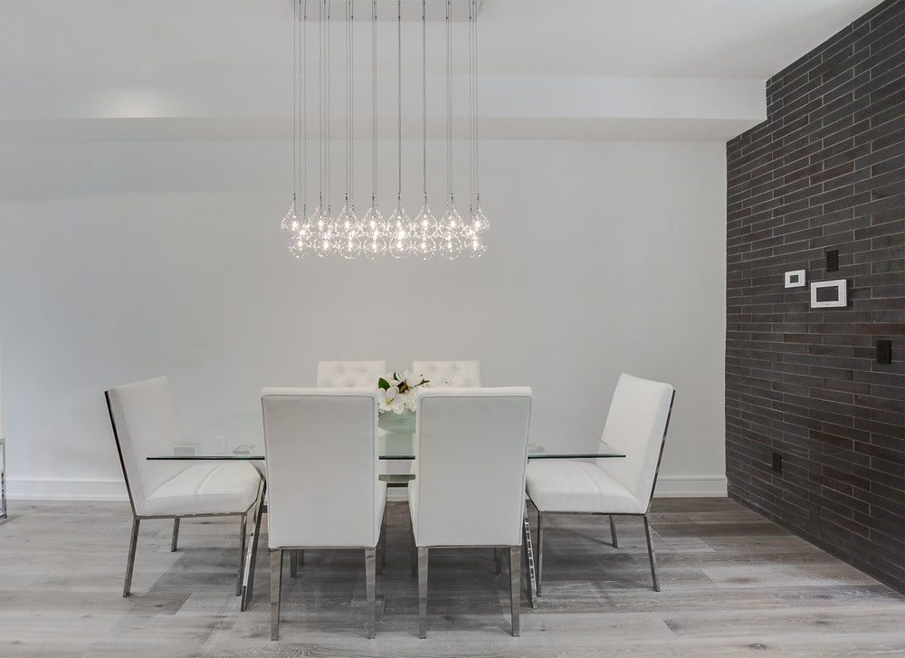 The dining area has a glass-top rectangular dining table surrounded by white modern chairs and topped with a modern decorative lighting.