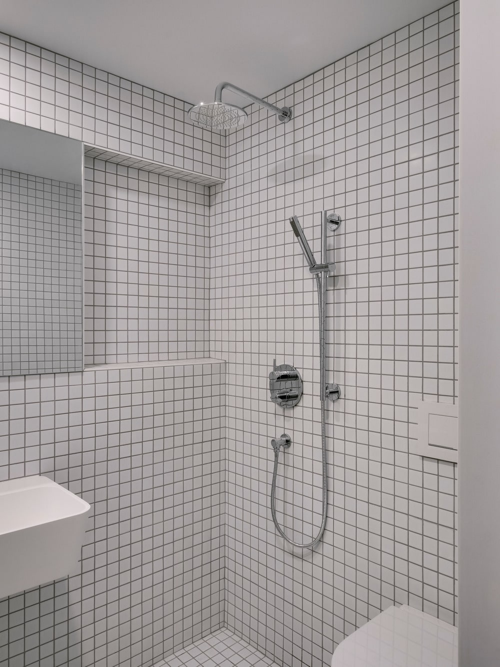 The bathroom has small white tiles on its walls that pair well with the floating sink and the toilet along with the fixtures of the shower area.