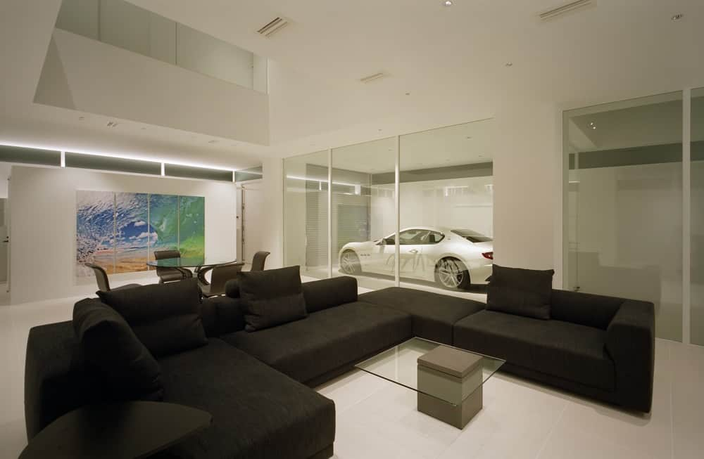 This is a close look at the minimalist living room that has a large black U-shaped sectional sofa and a glass-top coffee table surrounded by white walls, white tall ceiling and white flooring.