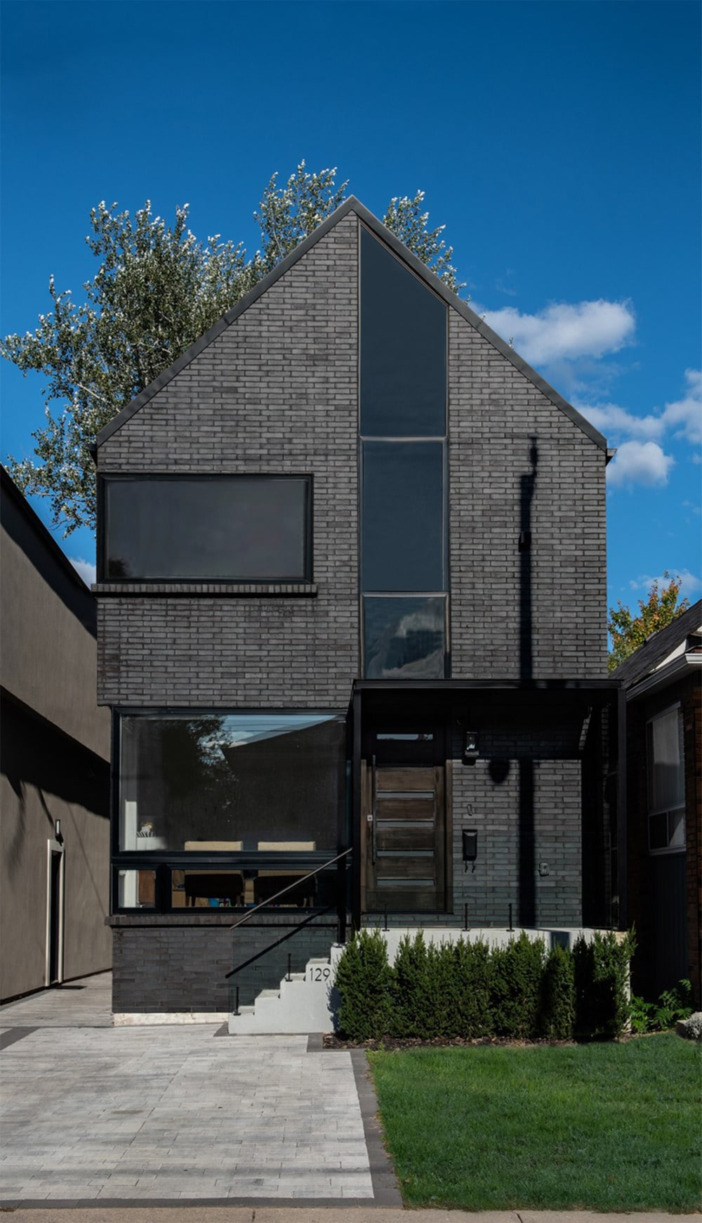 This is a view of the front of the house that has gray bricks and glass walls that give glimpses of the interiors of the house.