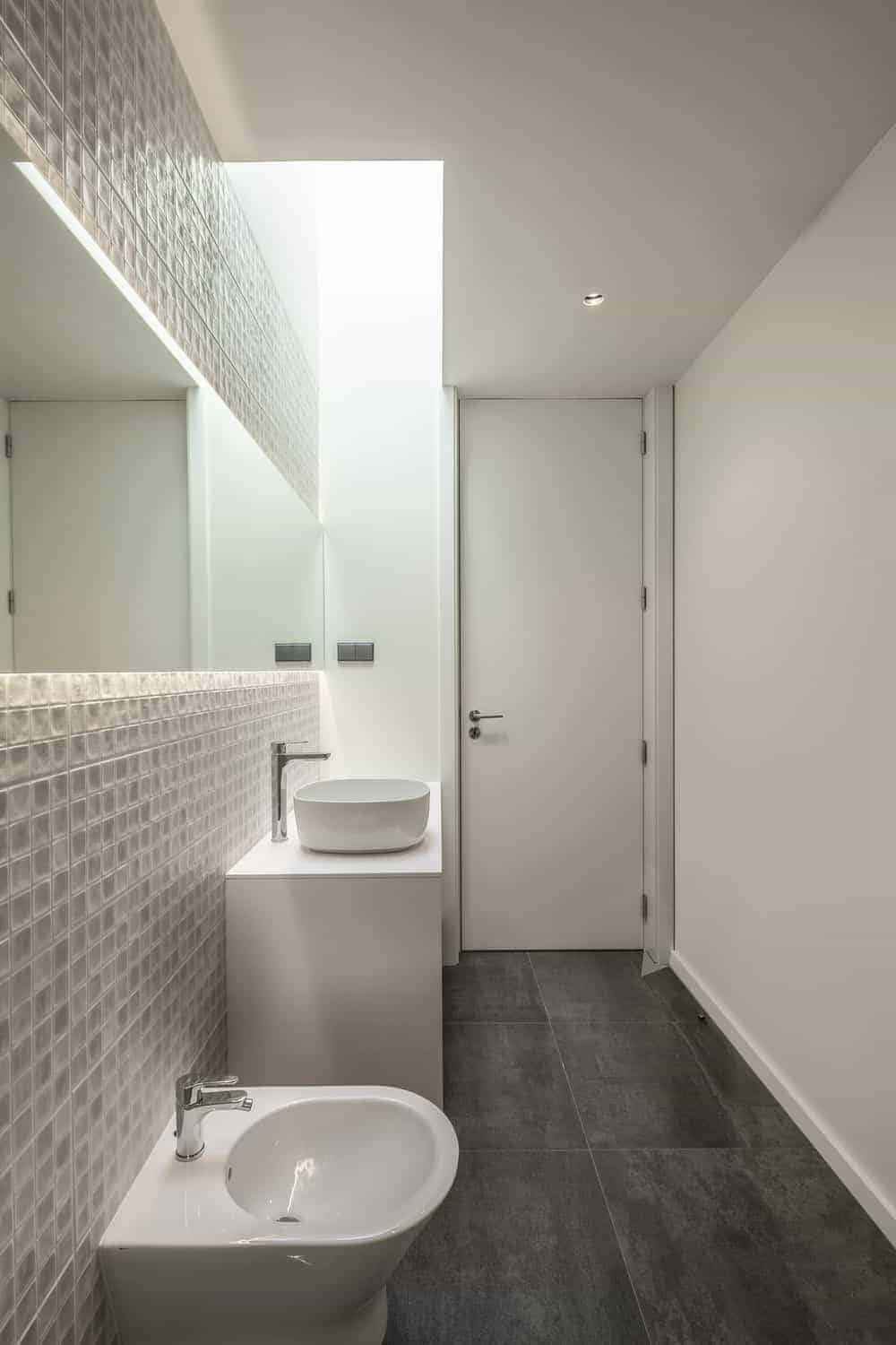 The bathroom has a dark gray flooring tiles that contrast the bright beige walls, tiles and the structure of the sink topped with a lit mirror that extends to the sides.