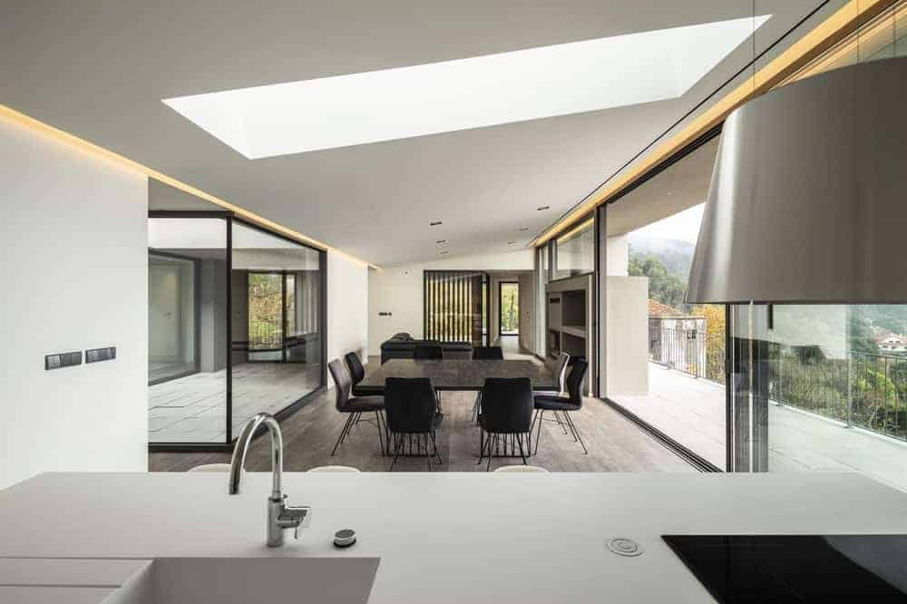 This is a view of the dining area from the vantage of the kitchen. It has a dark dining set contrasted by the white ceiling with skylight and the glass walls on both sides that bring in natural lighting.