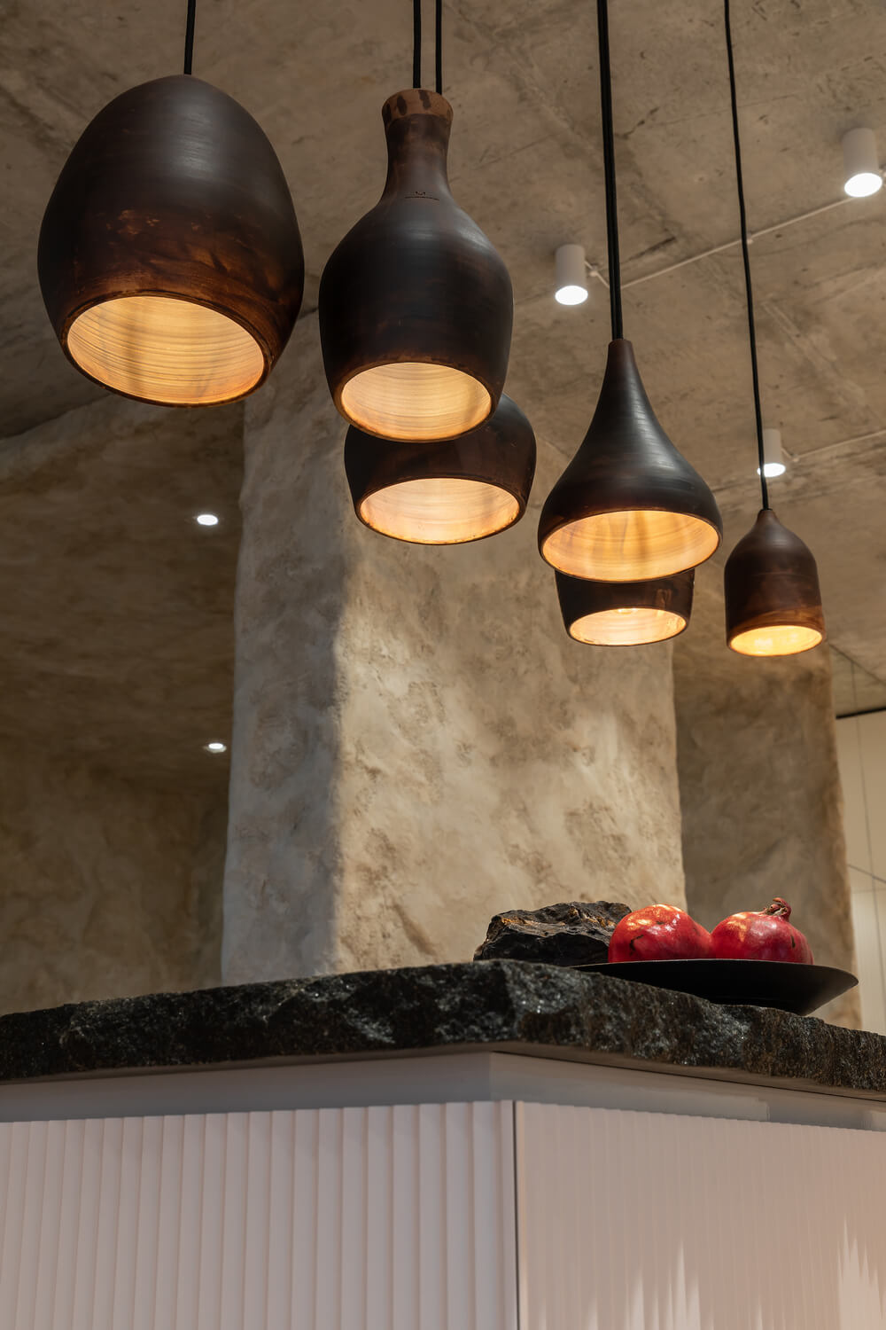 The kitchen island is topped with a collection of black pendant lights hanging from the concrete ceiling.