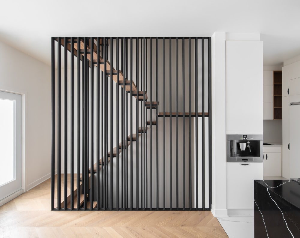 This is a close look at the staircase with a modern design to its floating steps and slatted panel.