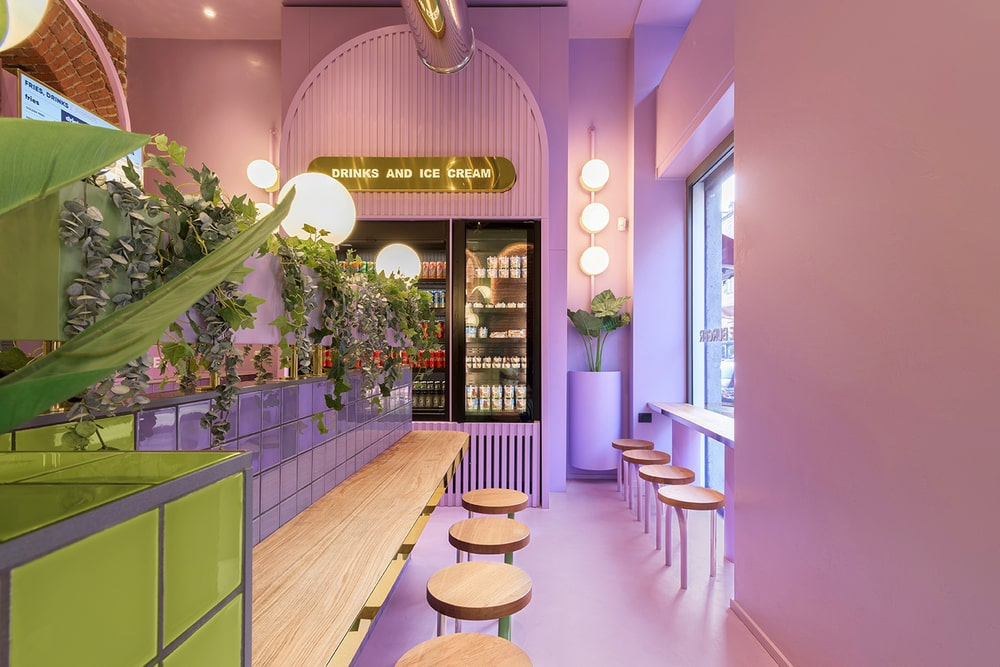 This is a side of the restaurant with bar stools and built-in wooden bars complemented by the purple tone of the floor, walls and ceiling adorned with vines and warm lighting.