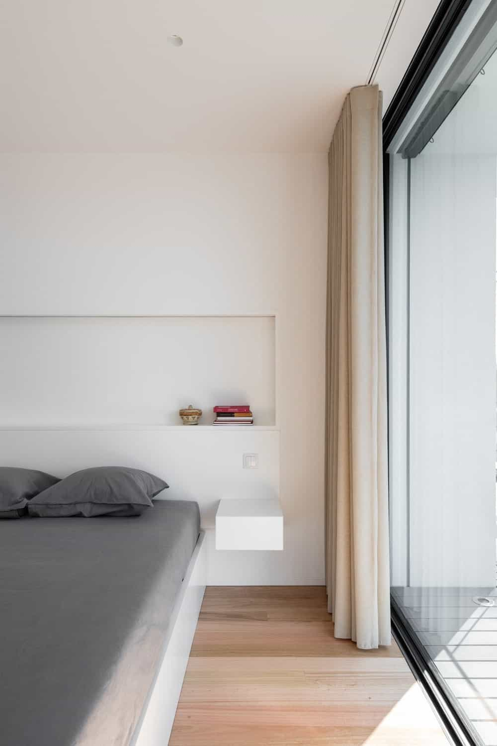 This is a close look at the minimalist bedroom that has a built-in white wooden platform bed topped with an alcove shelf and has a built-in white bedside table.