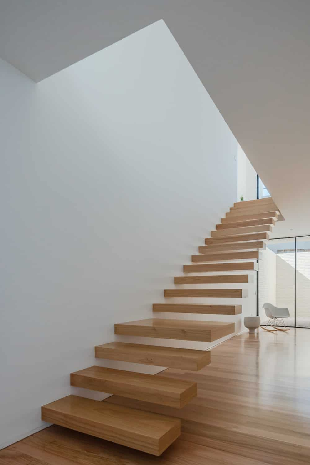 This is a look at the foyer that has a light hardwood flooring that matches with the wooden steps of the floating stairs. These are then complemented by the white walls and ceiling.