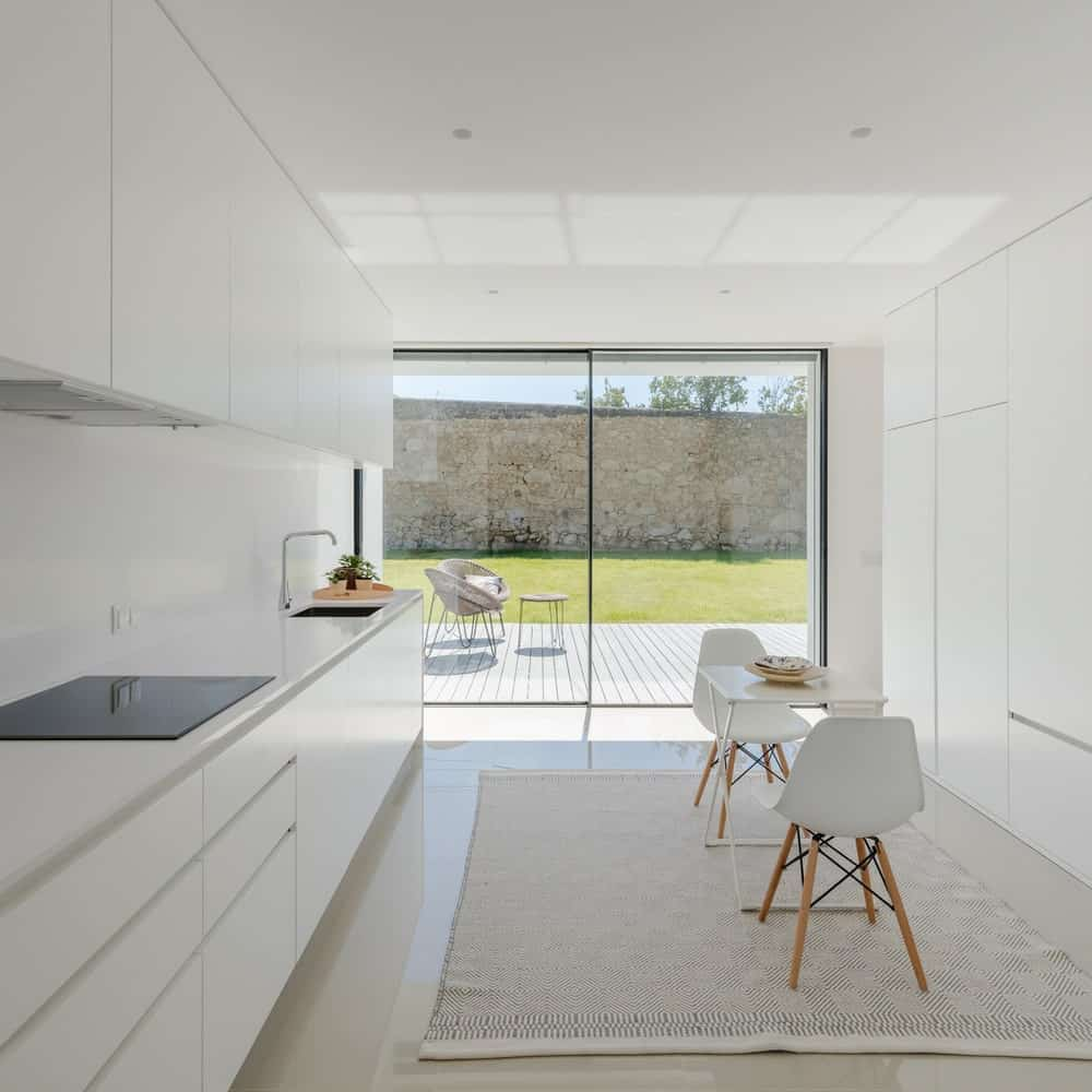 This is a bright white eat-in kitchen with consistent white modern tones on its cabinetry and breakfast nook brightened by the natural lights of the glass wall.