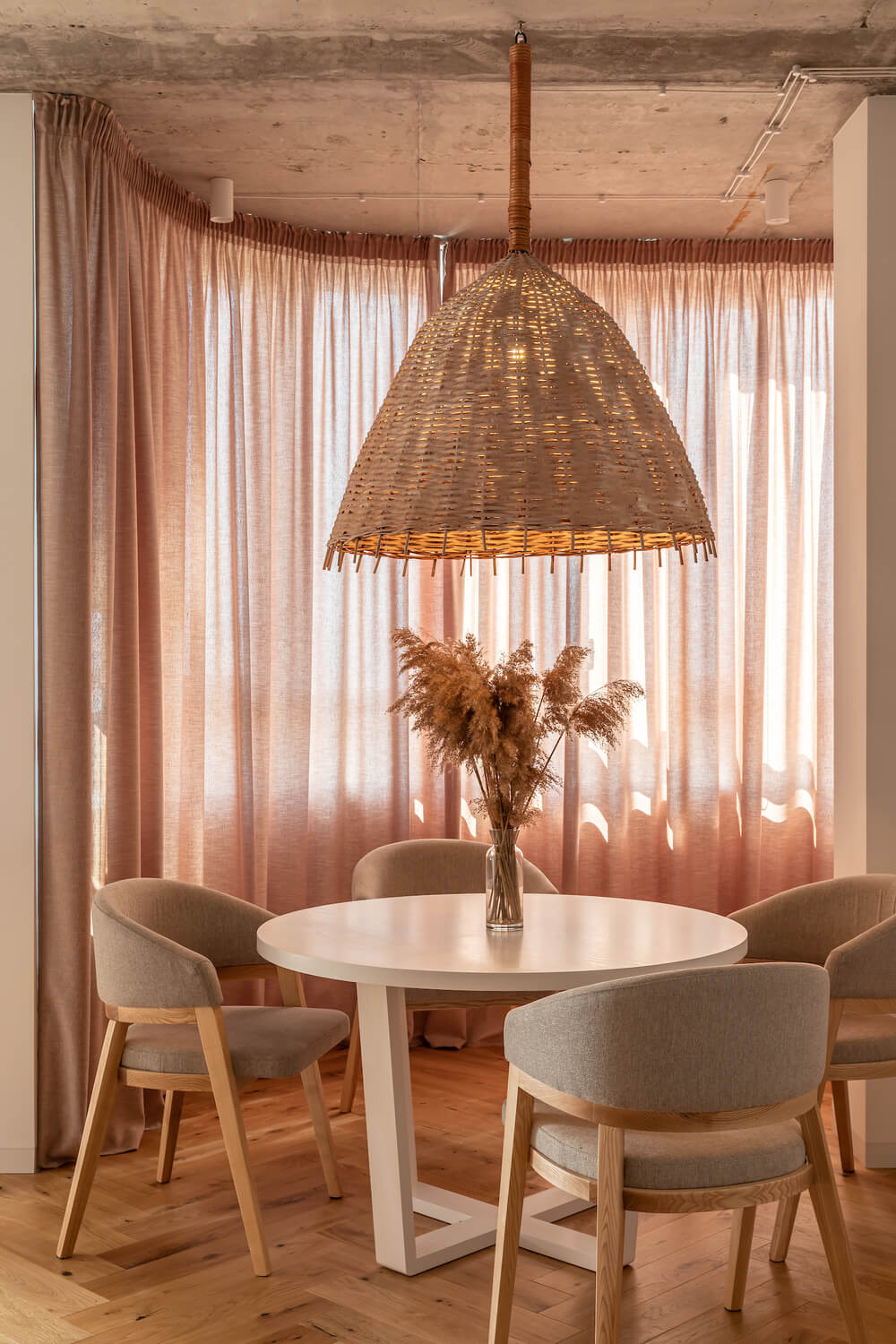 The dining area's round white table is surrounded by gray cushioned chairs and complemented by the pink curtains.