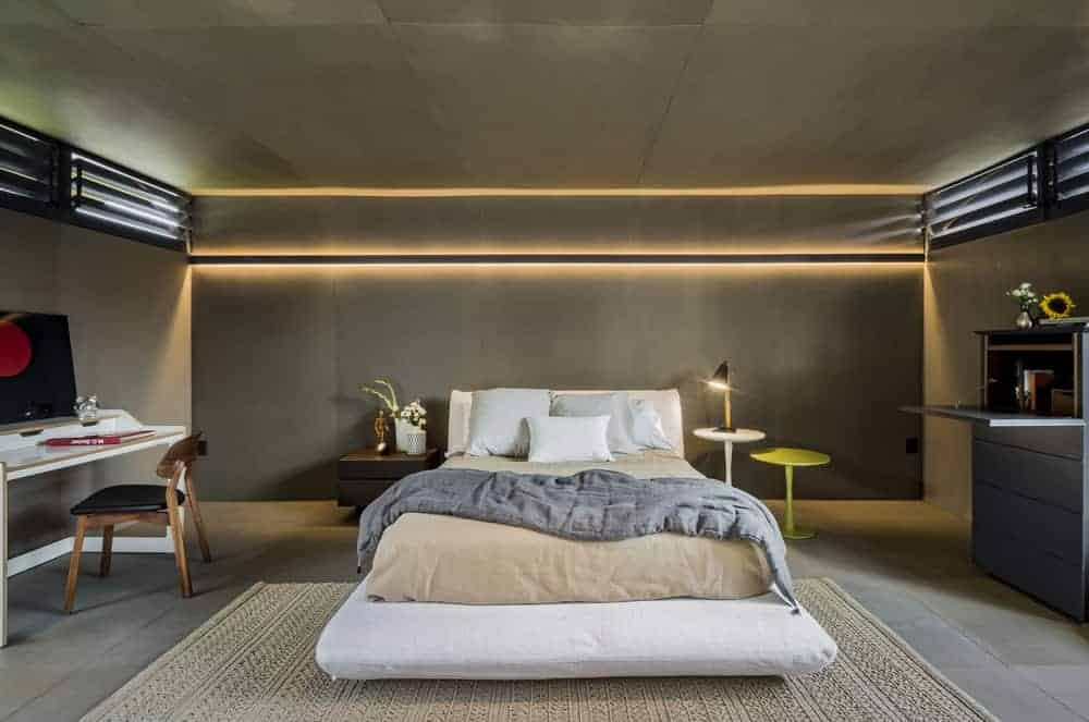 This is a look at the primary bedroom that has concrete walls, floor and ceiling adorned by the modern lighting above the white bed flanked by various bedside tables.