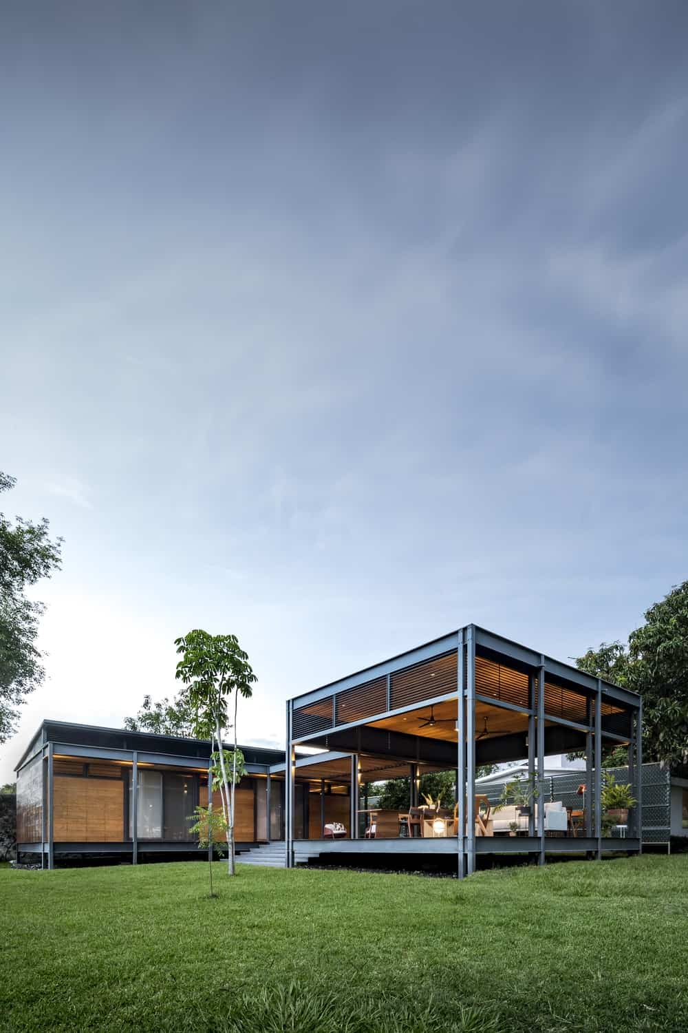 This is a look at the exterior of the house that has metal frames complemented by the surrounding minimalist landscaping of grass lawns and trees.