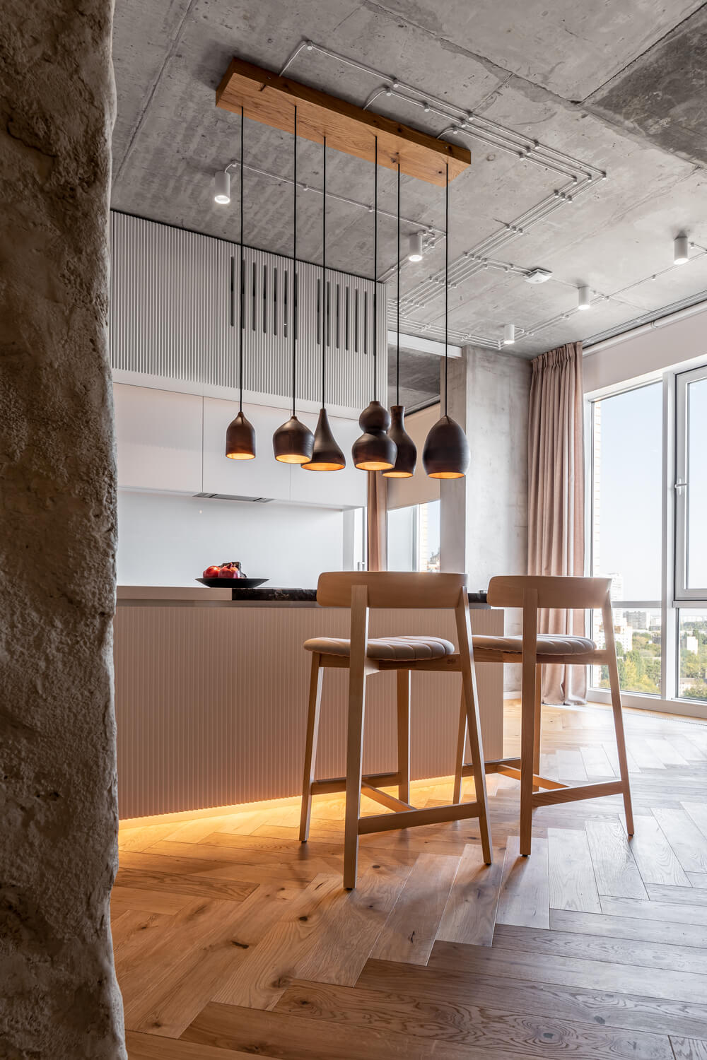 The kitchen is topped with a collection of pendant lights in different shapes and paired iwth a couple of wooden stools.