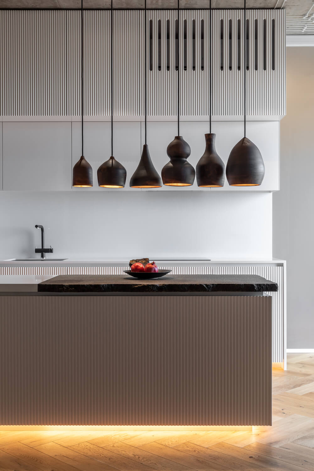 This close view of the edge of the kitchen island showcases more of the thick rough cut countertop and the different shapes of the pendant lights.