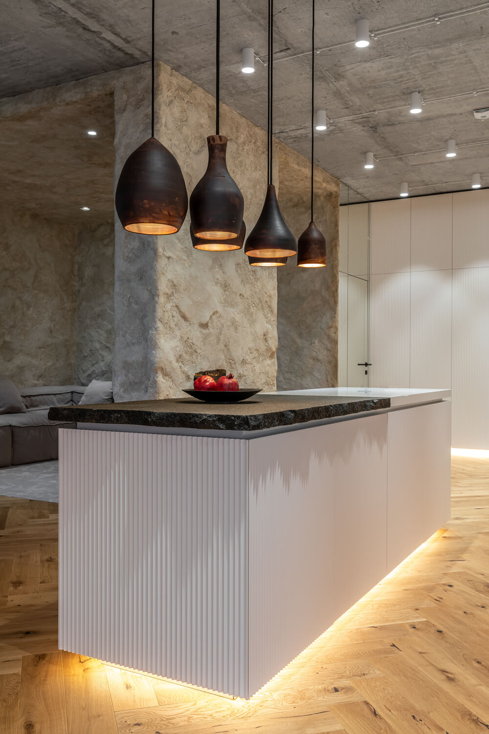 This is another view of the kitchen island showcasing more of its modern lighting underneath and its proximity to the living room walls.