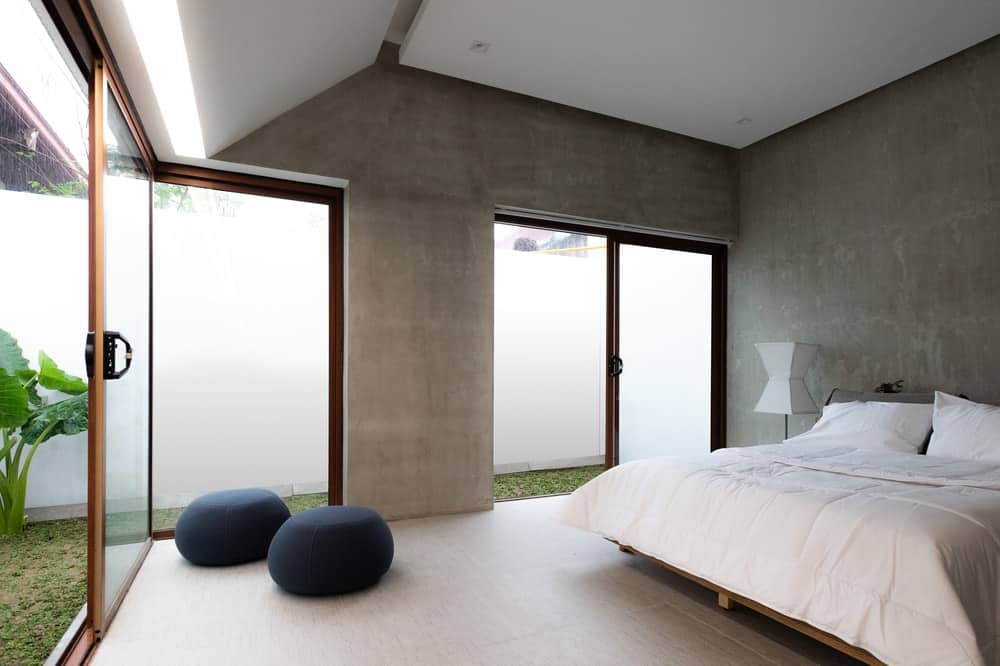 This is a look at the primary bedroom that has gray and white tones on its walls and ceiling to match the white bed brightened by the glass doors.