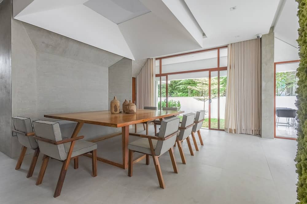 This is a look at the dining room of the house with neutral gray and white tones complemented by the wooden accents coming from the table and frames of the glass doors.