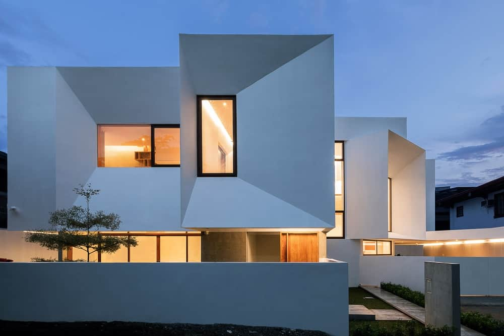 This is a look at the house exterior that has consistent white exterior walls complemented by the warm glow of the windows and the landscaping of shrubs, concrete walkways and grass.