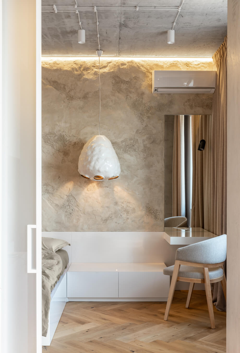On the side of the floating white vanity table is a bench that can also be used as a bedside table.