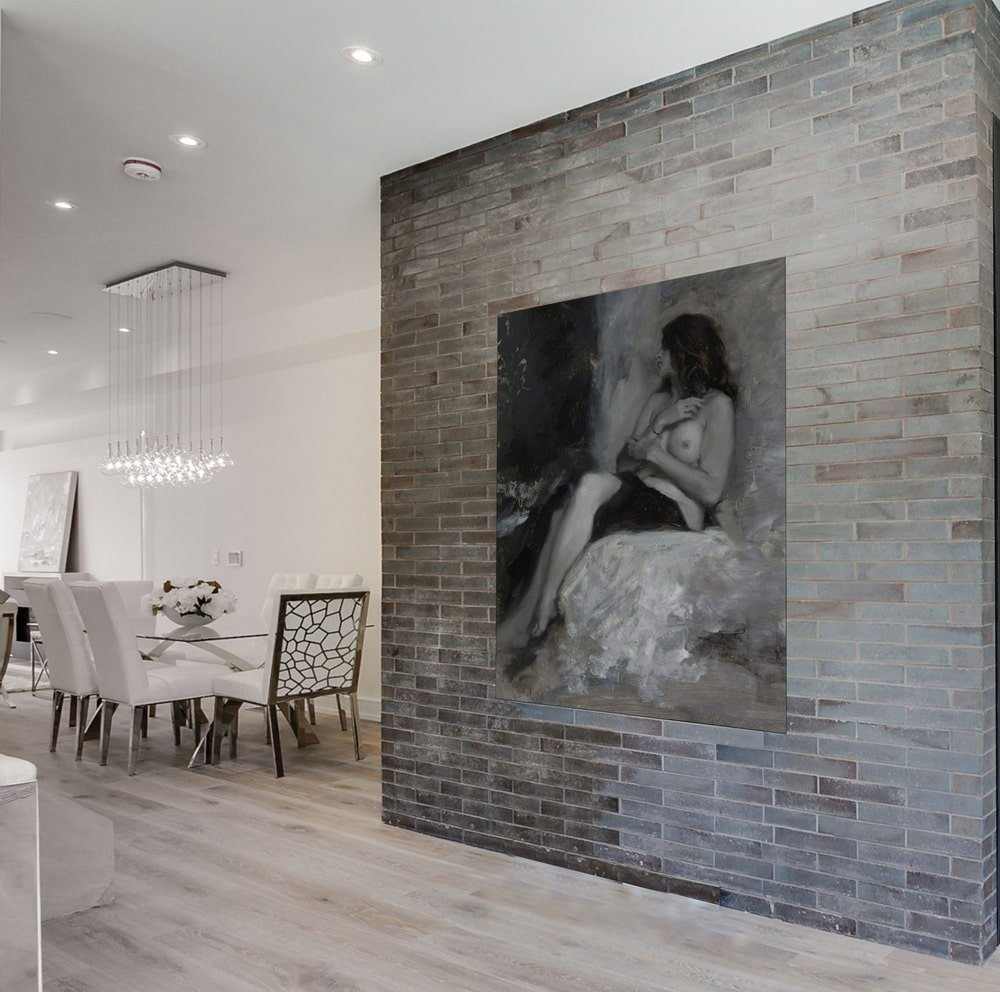 On the side of this living room is a large brick wll adorned with a large wall-mounted artwork that pairs well with the gray tone of the brick wall.