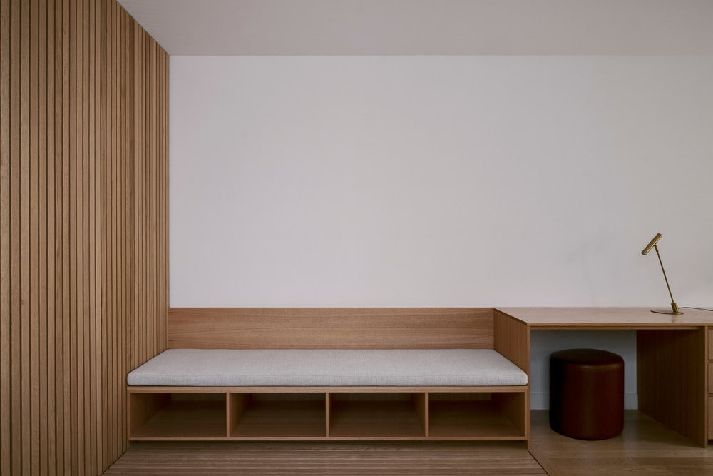 This is a close look at the living room that has a built-in wooden sofa with shelves below and attached to the wooden slatted panel on the side.