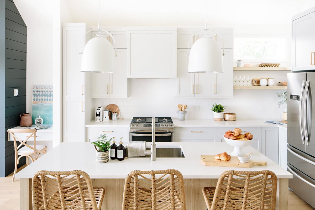The kitchen is equipped with stainless steel appliances, a breakfast island, an e-space, and white cabinetry accentuated with brass hardware.