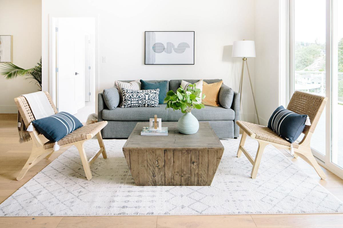 Living room with a gray sofa, wicker chairs, and a rustic coffee table that sits on a patterned area rug.