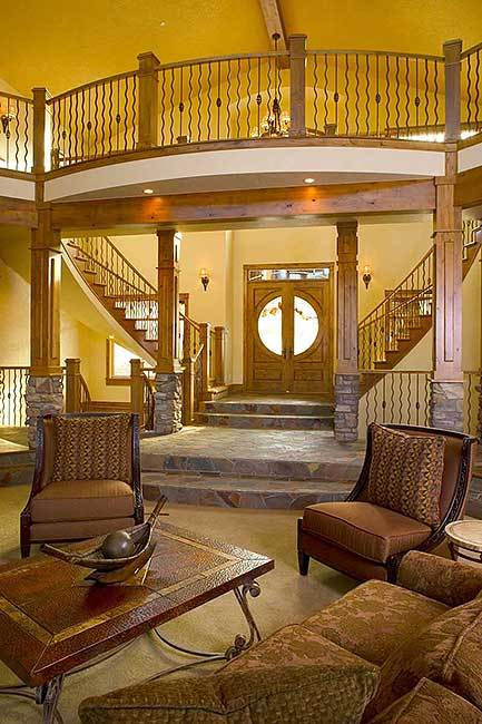This is a full view of the foyer from the vantage of the living room showcasing the wooden double door that matches the wooden structures like the dual curved staircases and the pillars complemented by the mosaic stone floor.