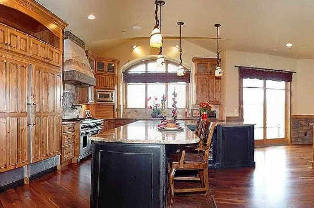 This is a full view of the kitchen that has rustic wooden cabinetry lining the walls that match the hardwood flooring. These are complemented by the large L-shaped black kitchen island topped with pendant lights.