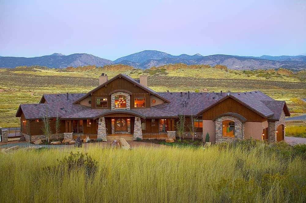This is an exterior view of the mountain chalet-style home with dark wooden exterior walls complemented by the landscaping of shrubs, decorative rocks and stone mosaic accents.