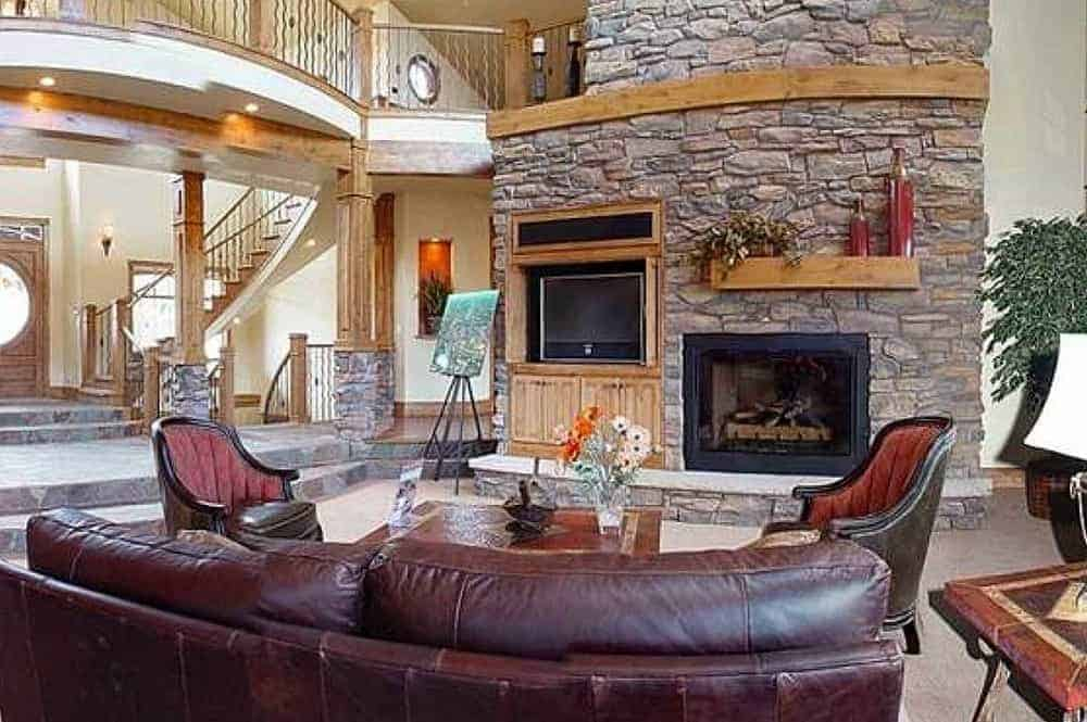 This large living room is dominated by the tall mosaic stone wall that houses the TV and the fireplace across from the large leather sofa set and wooden coffee table.