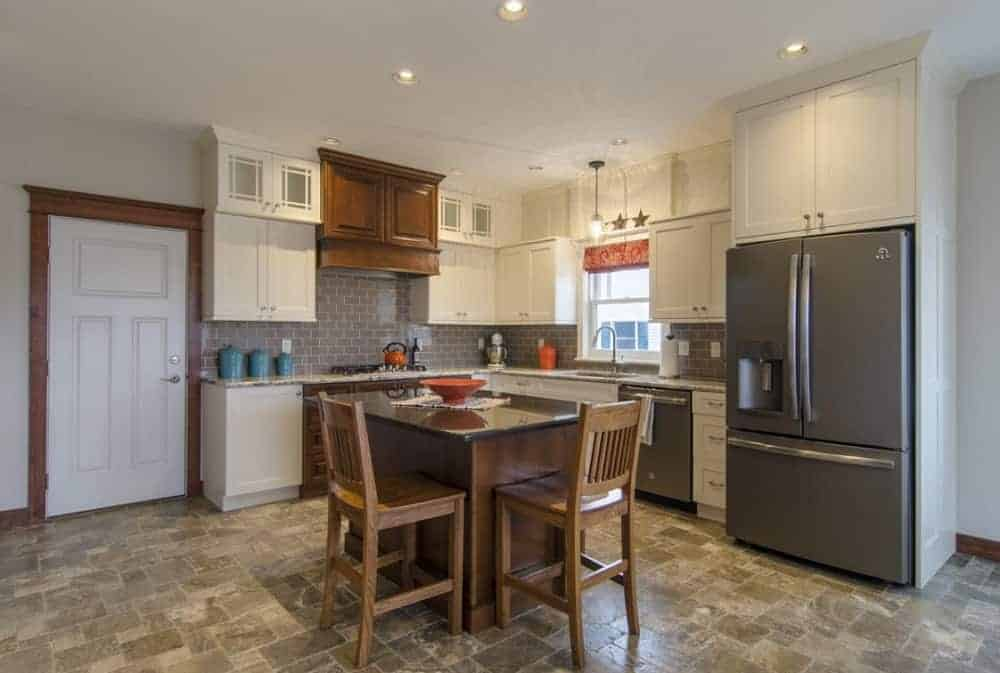 The kitchen is complemented by the earthy tone of its flooring tiles that go well with the small kitchen island, beige cabinetry and the stainless steel appliances.