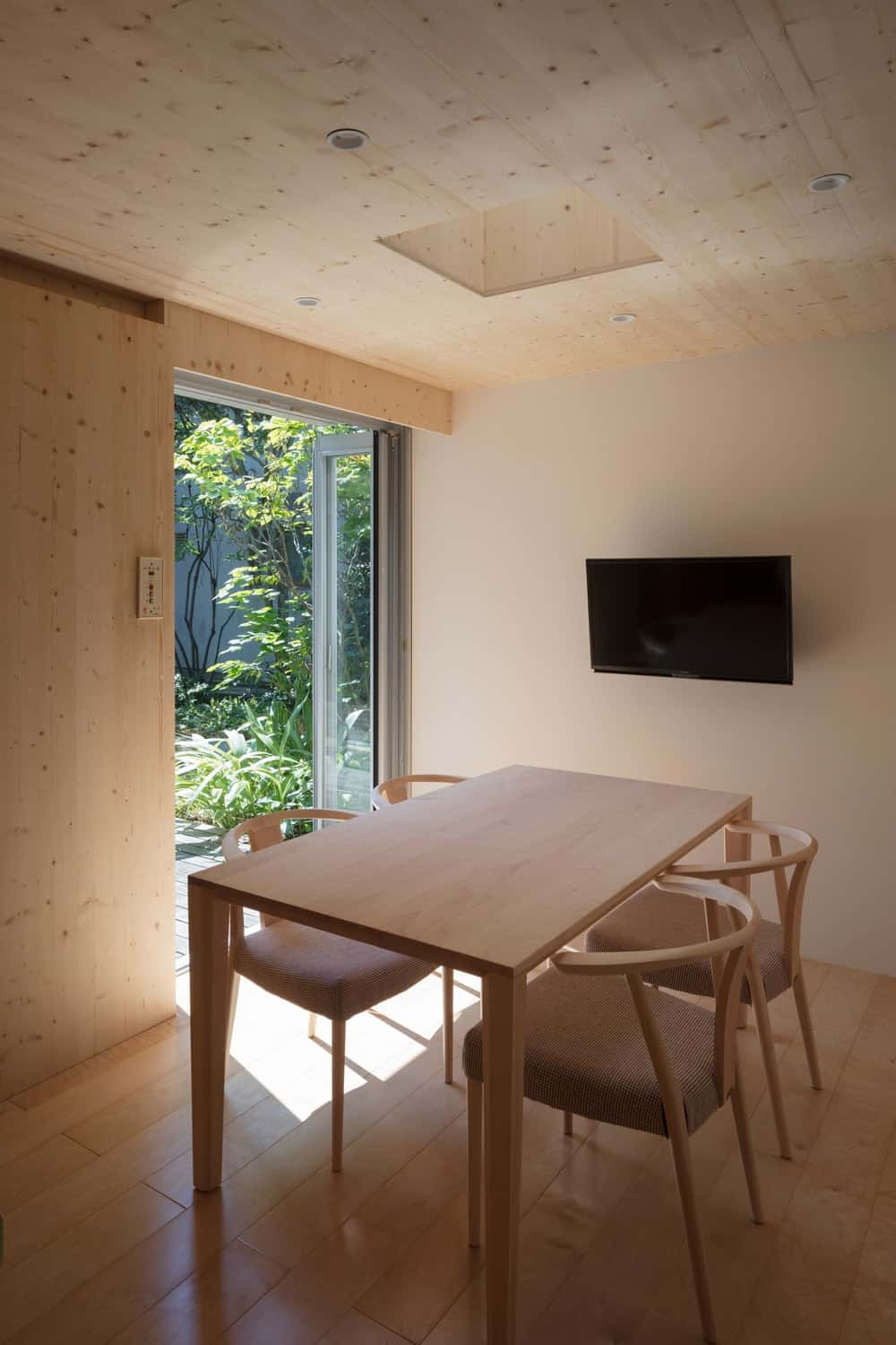 This is a close look at the simple minimalist dining area with consistent light wooden tones on its walls, ceiling, sliding door and the wooden dining table surrounded by wooden wishbone chairs.