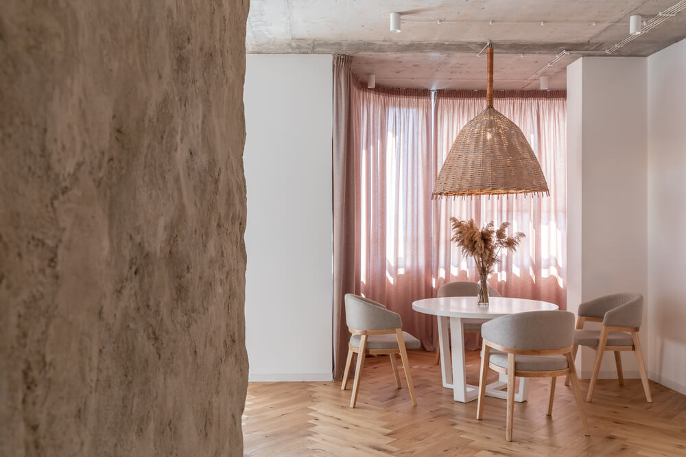 The dining area has a round white dining table surrounded by gray cushioned chairs brightened by the pink curtains that filter the light.