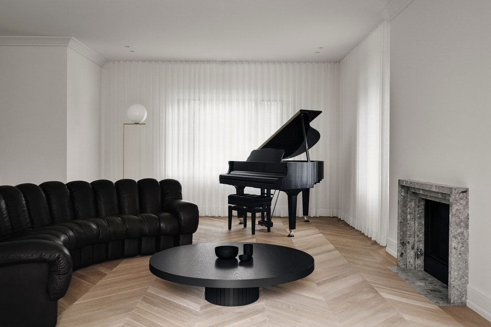 This is a simple minimalist living room that has a large curved black tufted sofa paired with a black round coffee table and grand piano. These are contrasted by the bright white walls and white ceiling.
