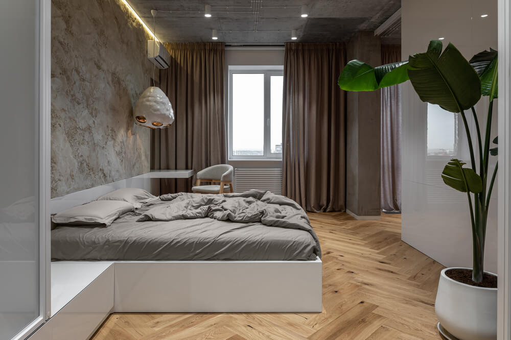 The other side of the bed also has a built-in bedside table that extends to the cabinet on the side. These are then complemented by the large textured stone wall.