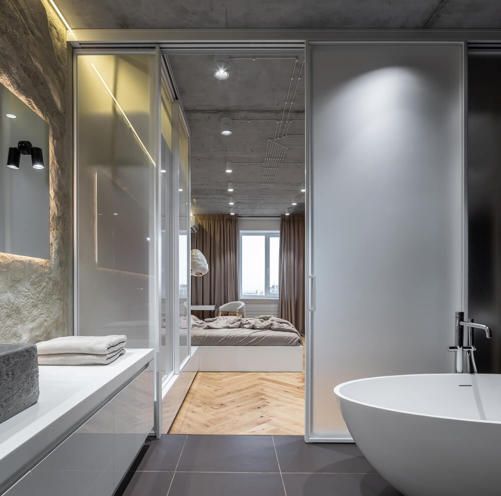 The bathroom has a freestanding white porcelain bathtub across from the white modern vanity topped with a large wall-mounted mirror.