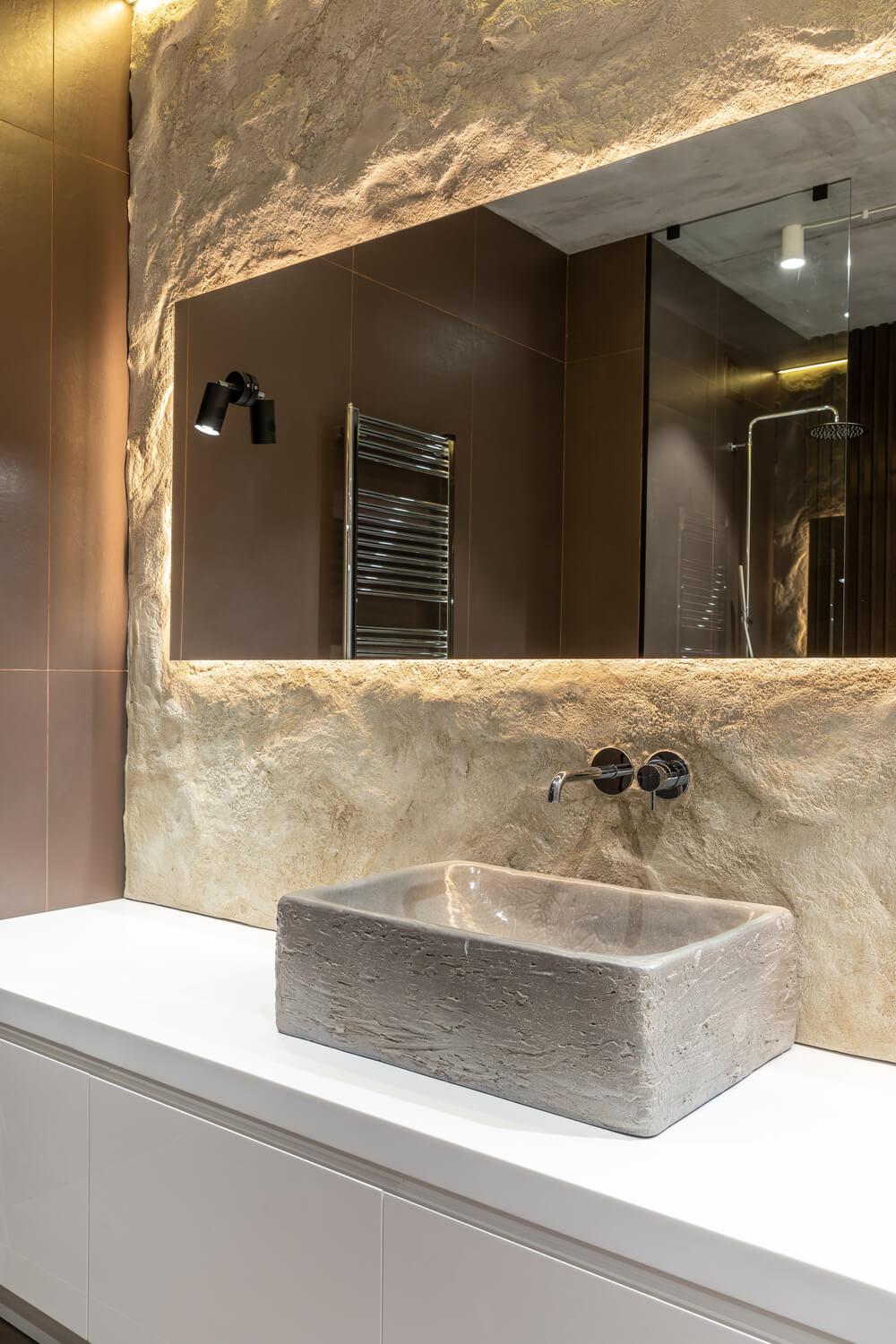 This is a close look at the rough textured structure of the sink that matches the textured stone wall adorned with the mirror's modern lighting.