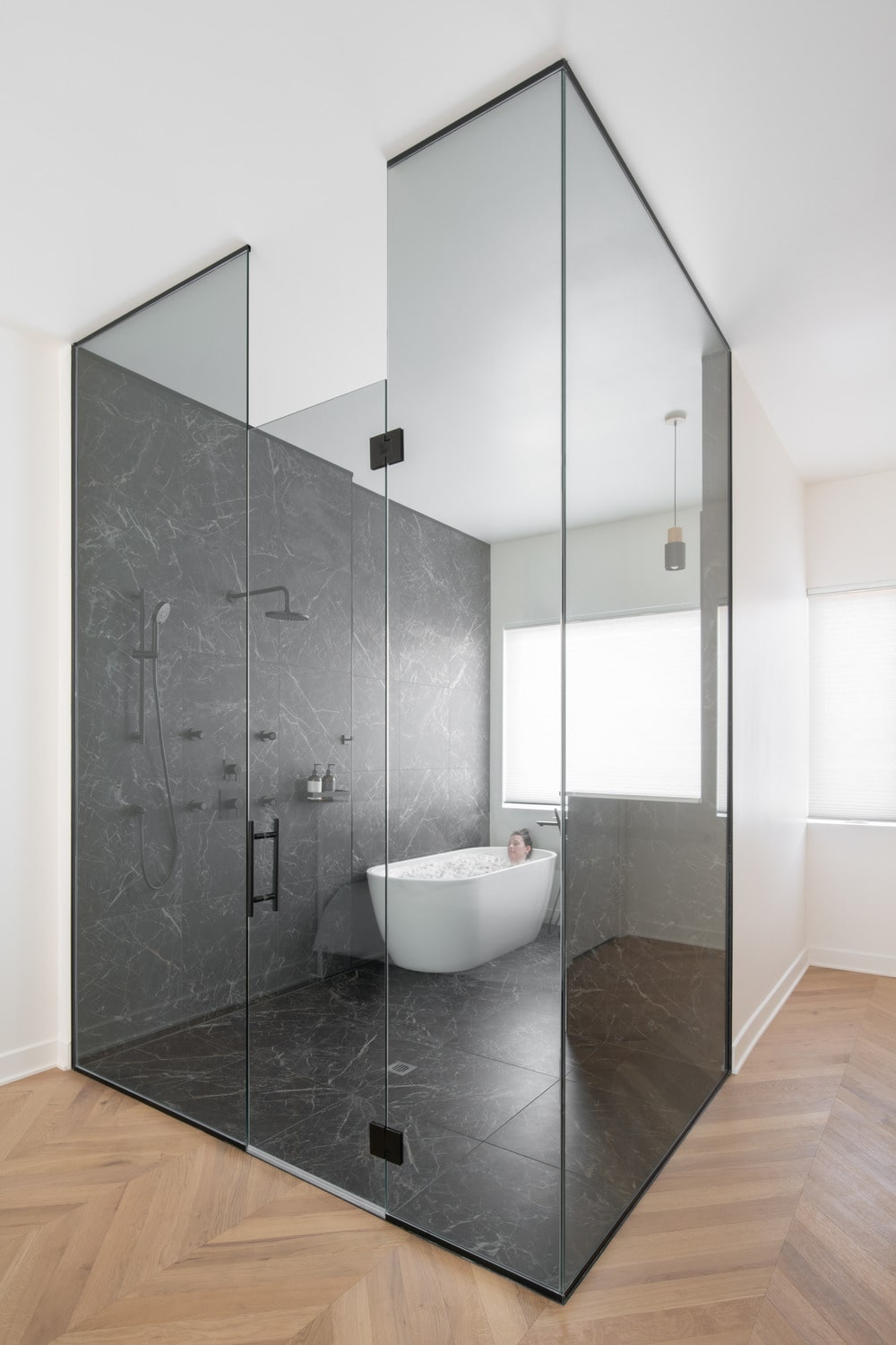 This is another look at the glass-enclosed bathroom that has a freestanding bathtub by the corner windows and a vanity on its other side.