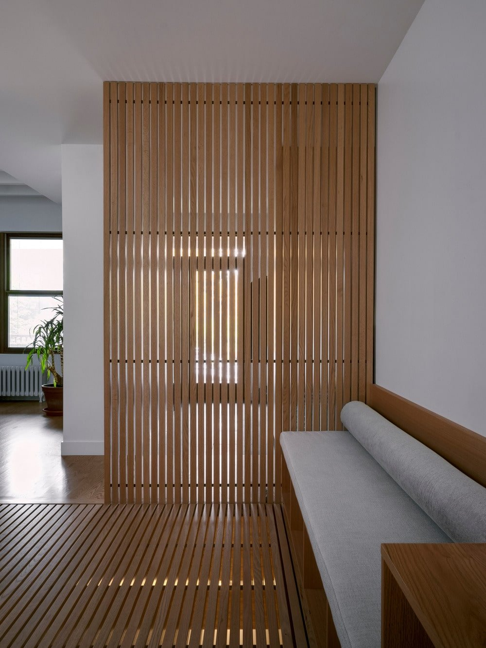 This is a closer look at the wooden slatted panel that extends its design to the flooring.