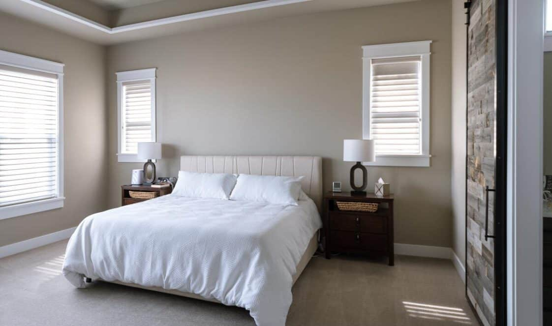This is a simple primary bedroom with beige walls, tall windows and a beige tufted bed flanked by brown wooden bedside drawers. These are then complemented by the rustic mosaic wooden sliding door.