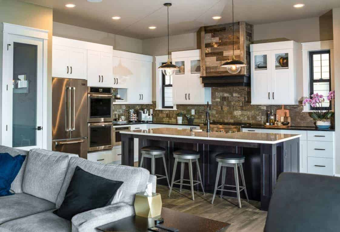This kitchen has white cabinetry and stainless steel appliances that stand out against the brown wooden tones of the backsplash and the vent hood that has a rustic aesthetic.