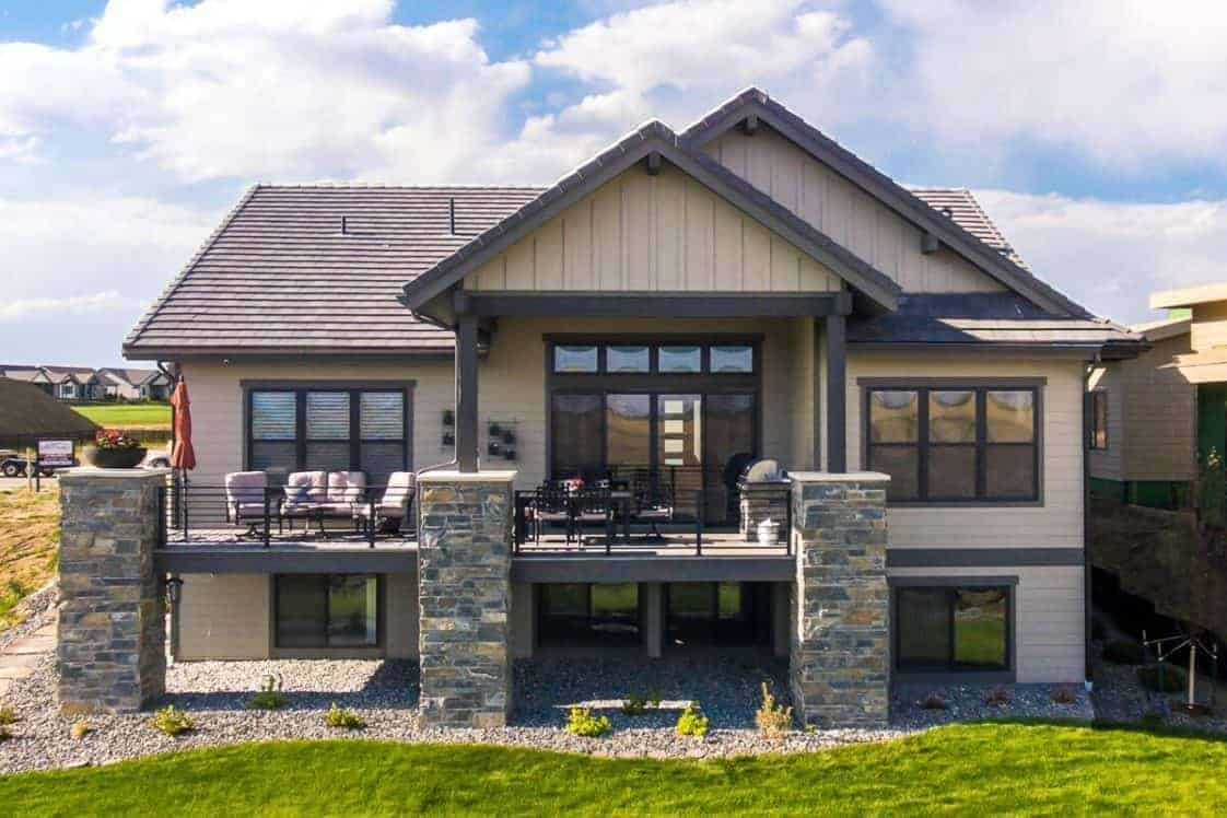 This is a look at the back of the house that is supported with large stone mosaic pillars that go well with the landscaping of graveled soil, shrubs and grass lawn.