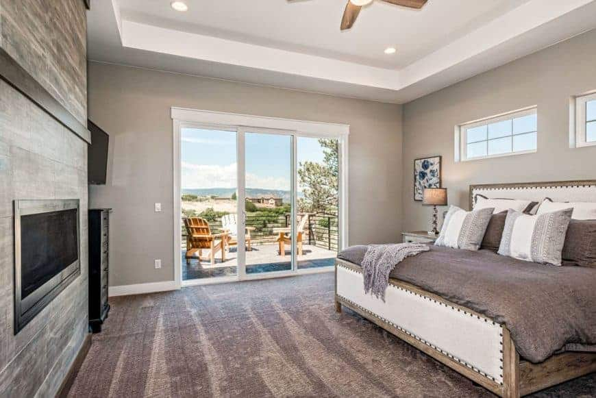 This is the primary bedroom with a large wooden structure that houses the modern fireplace across from the large bed with a cushioned headboard.