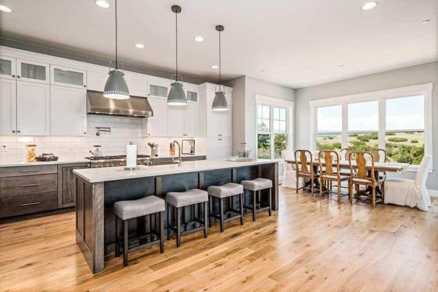 This is a close look at the spacious eat-in kitchen with a wooden dining set on the far side by the dark kitchen island with a white counter that matches the cabinetry and subway tiles.