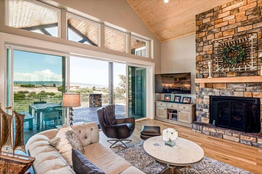 This is a close look at the living room with a cozy beige sofa and brown leather armchair by the circular wooden coffee table across from the stone mosaic fireplace with a floating wooden shelf on top.