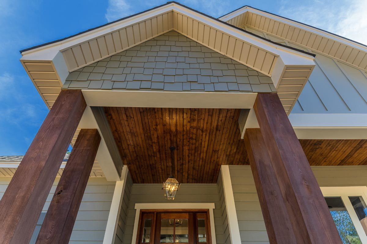 A close-up look at the home entry showing its wooden columns and gable roof adorned with shake accents.