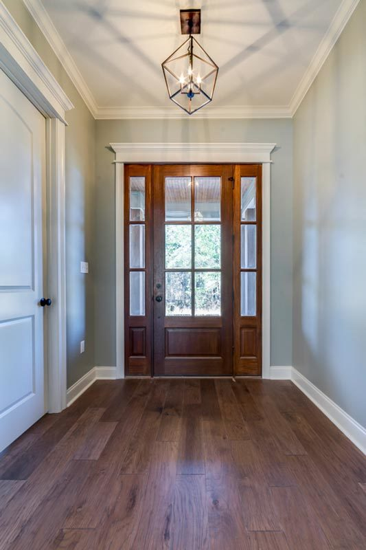 The foyer has a glazed entry door and a wrought iron chandelier that emits a warm ambiance for a great impression.