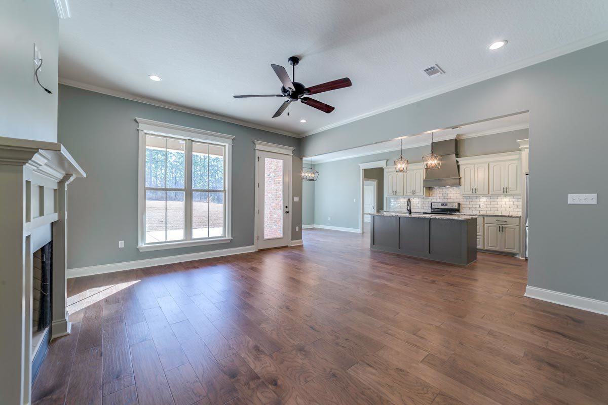 Spacious living room with hardwood flooring that runs throughout the open kitchen and dining space.
